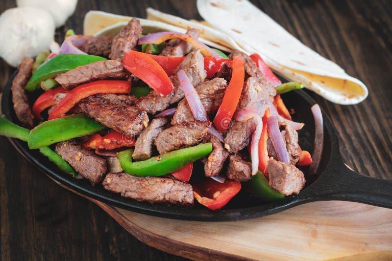 Ny varm Fajita för nötköttbiff i gjutjärnpanna royaltyfria bilder