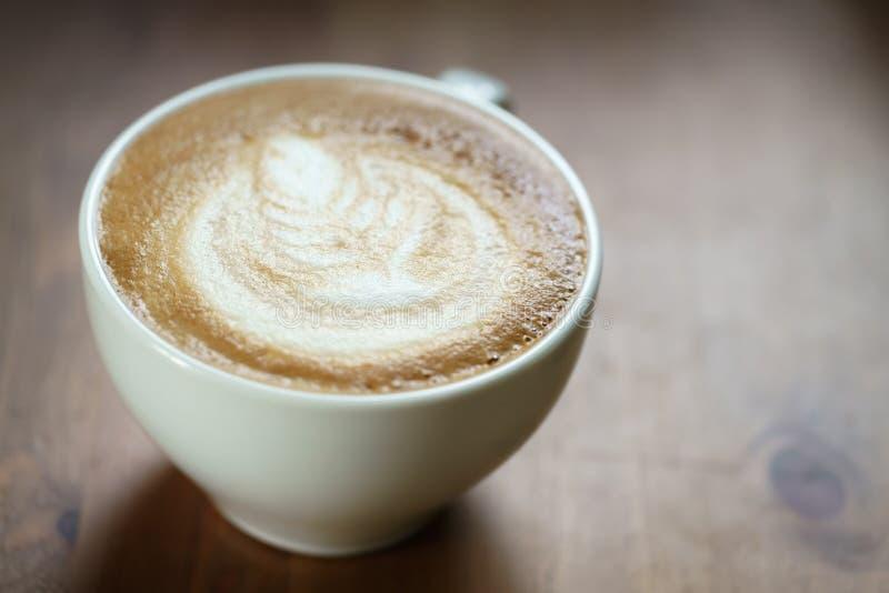 Ny varm kopp av coffe med lattekonst på den wood tabellen royaltyfri foto