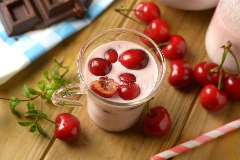 Ny yoghurt med röda körsbär i den glass koppen royaltyfri foto