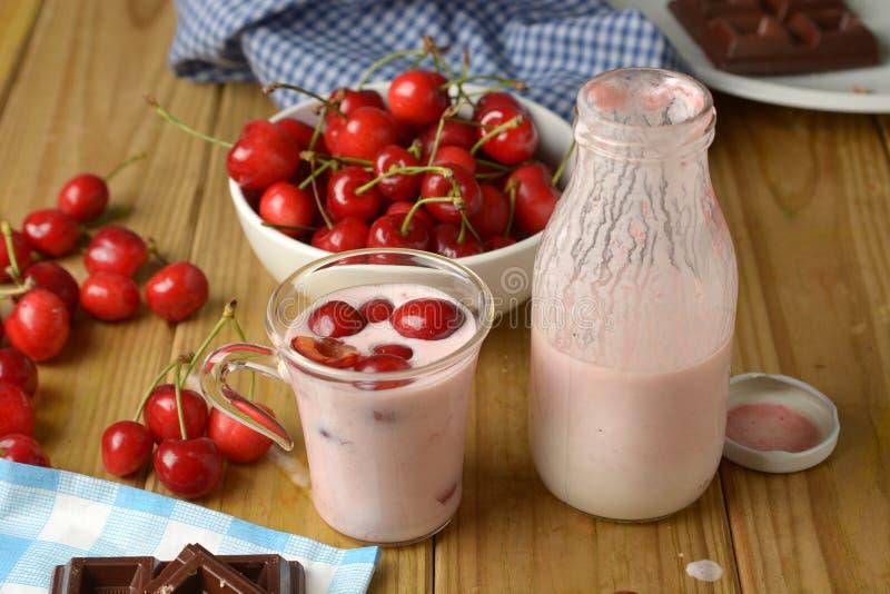 Ny yoghurt med röda körsbär i den glass koppen arkivfoto