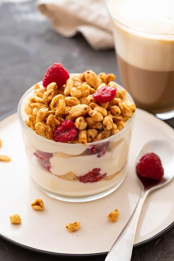 Ny yoghurt med rasberries och kaffe i klart exponeringsglas Hallon i den vita bunken Sund morgonfrukost royaltyfri foto