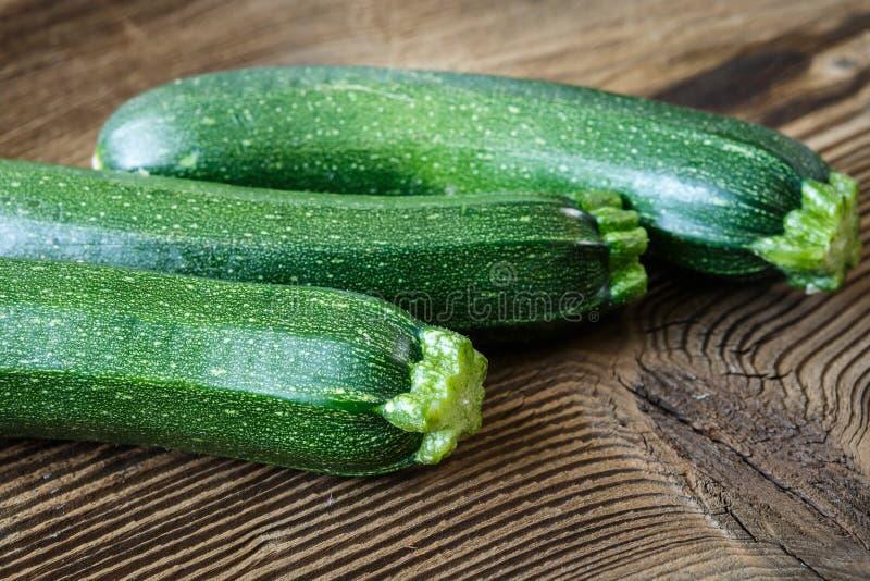 Ny zucchini på skärbräda, på träbakgrund royaltyfria foton