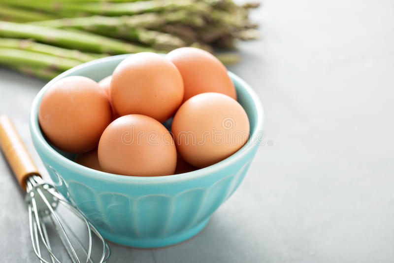 Nya ägg i en bunke med viftar arkivfoto