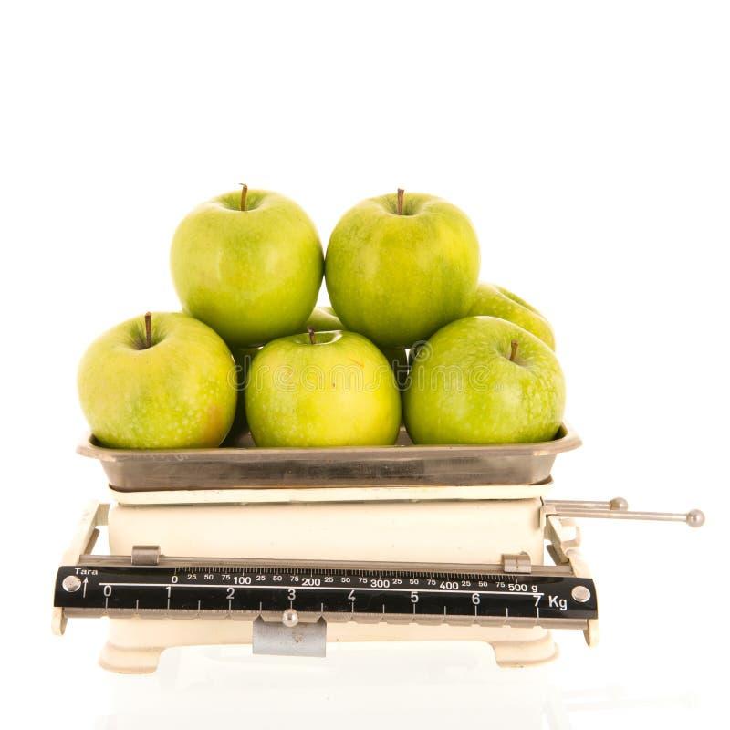 Nya äpplen för viktskala som isoleras över vit bakgrund royaltyfri foto
