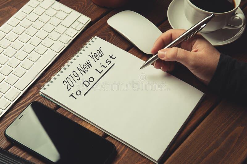 2019 nya år som gör listan - inskrift på notepaden på trätabellen och kvinnliga handen som är klara att skriva kontrollistan, royaltyfria foton