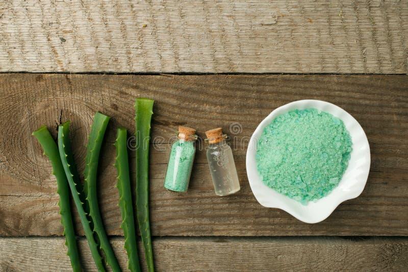 Nya aloevera sidor, den gröna aromatiska brunnsorten saltar och exponeringsglas av aloevera fruktsaft på träbakgrund arkivbild