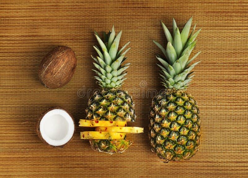 Nya ananors och kokosnötter på matt bambu royaltyfri foto