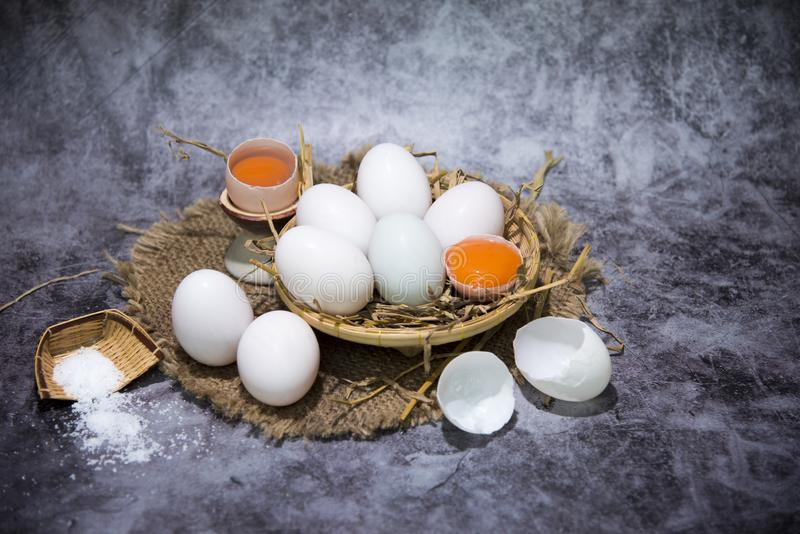 Nya andägg i sugrör och att salta på en korg för framställning av rimmade ägg för barn, äggbevarande broken ?gg ?ver white royaltyfri foto