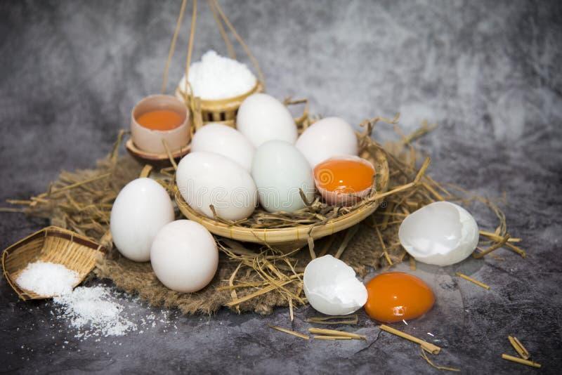 Nya andägg i sugrör och att salta på en korg för framställning av rimmade ägg för barn, äggbevarande broken ?gg ?ver white royaltyfria bilder