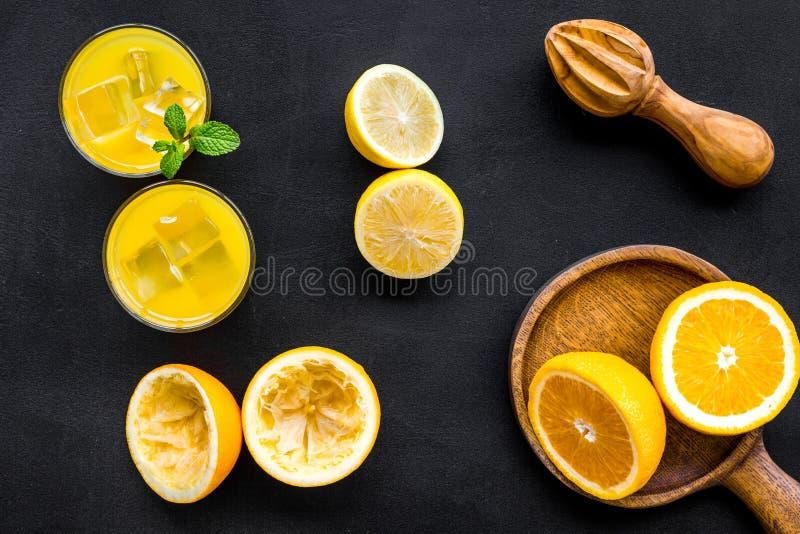 Nya apelsiner för åtstramning med juiceren Orange fruktsaft i exponeringsglas nära halva klippta apelsiner på bästa sikt för svar royaltyfria bilder