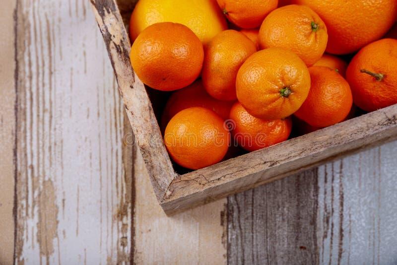 Nya apelsiner i en gammal träask På en träbakgrund fotografering för bildbyråer