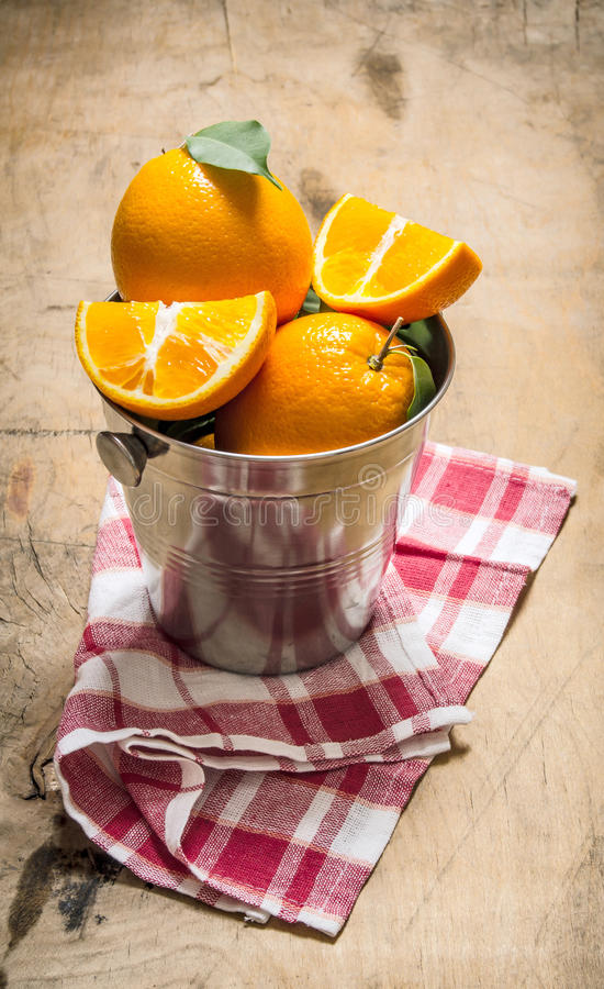 Nya apelsiner i hinken på tyget royaltyfria bilder