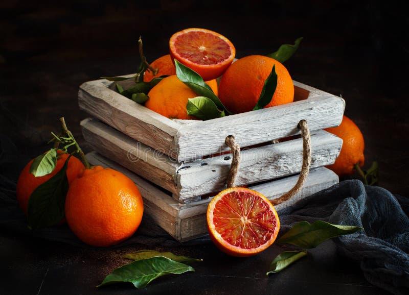 Nya apelsiner med sidor i en ask royaltyfri bild