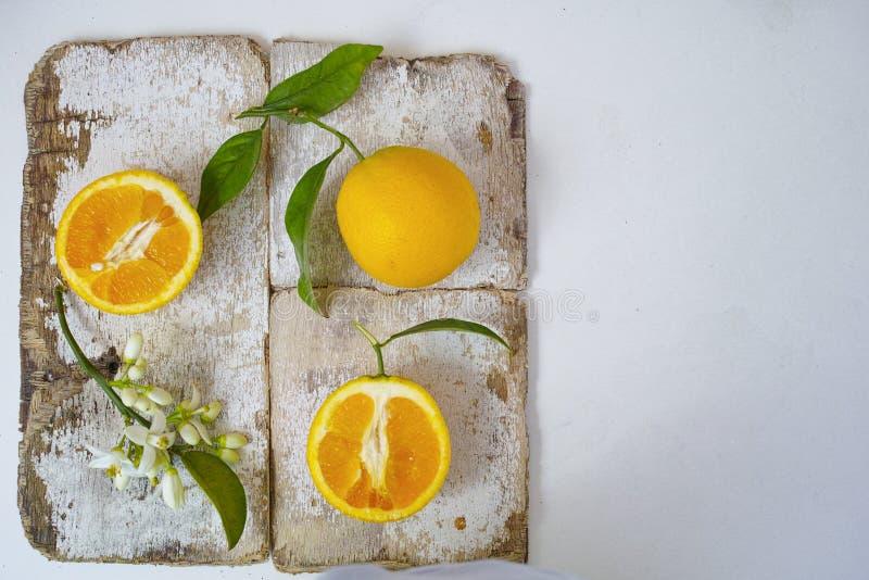 Nya apelsiner med sidor och blommor för orange träd på lantligt trä arkivfoton