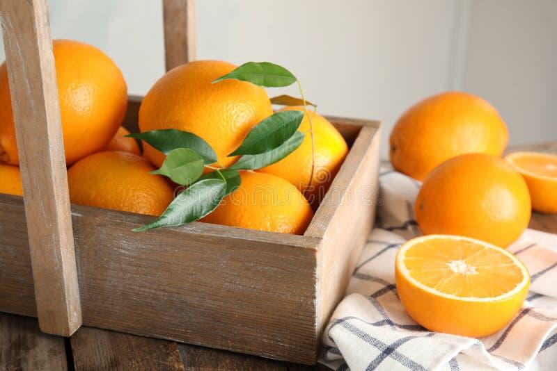 Nya apelsiner med sidor och den lantliga asken på tabellen arkivfoto