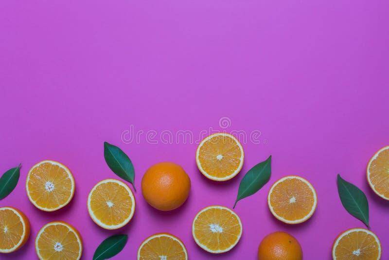 Nya apelsiner på den purpurfärgade bakgrunden royaltyfria foton