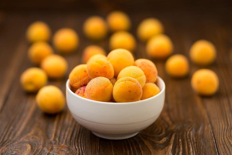 Nya aprikors i en platta på en träbakgrund, aprikors på a royaltyfri foto