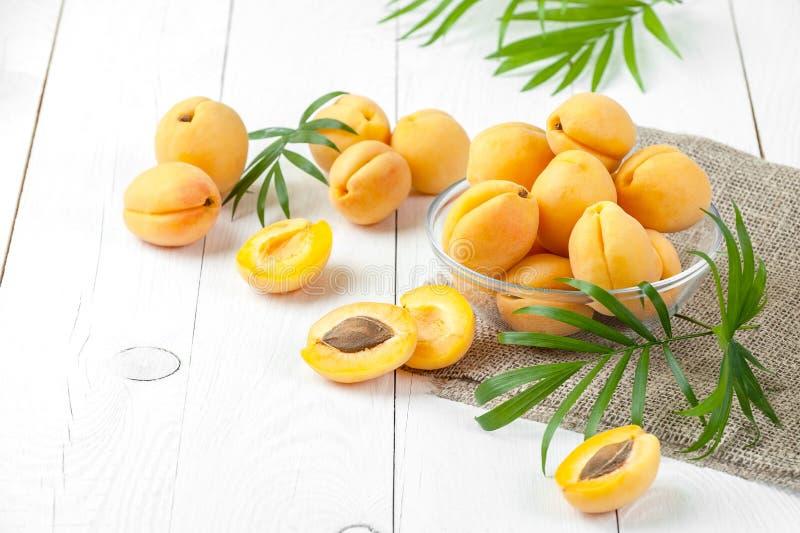 Nya aprikors i ett runt glass pial på en närbild för vitt bräde fotografering för bildbyråer