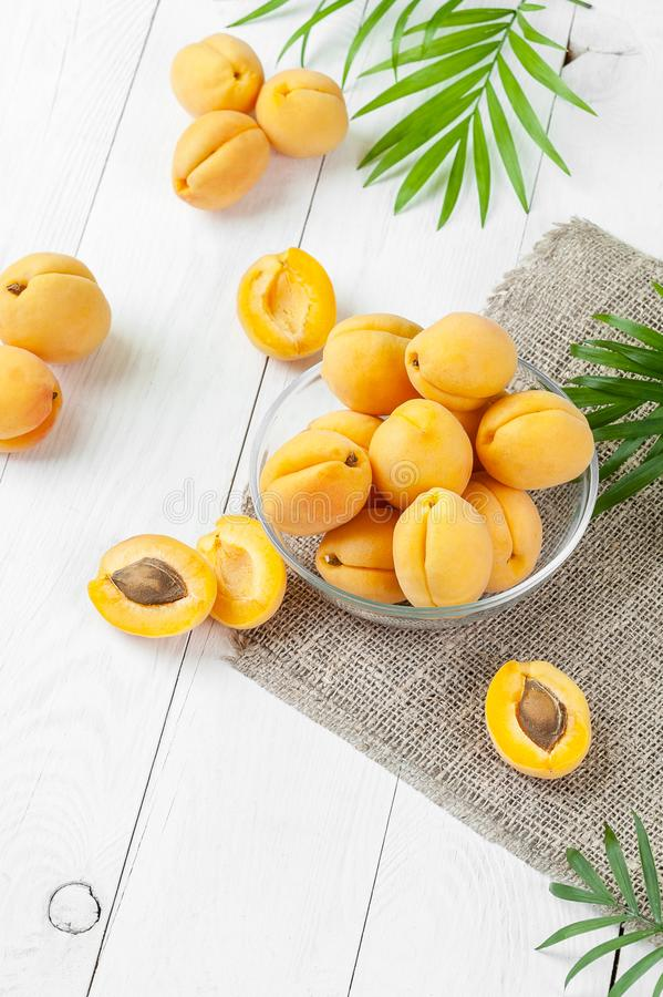 Nya aprikors i ett runt glass pial på en tabell för vitt bräde arkivfoton