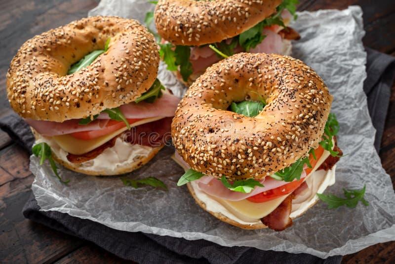 Nya baglar skjuter in med gräddost, bacon, tomaten och den gröna lösa raket på den lantliga trätabellen royaltyfria bilder