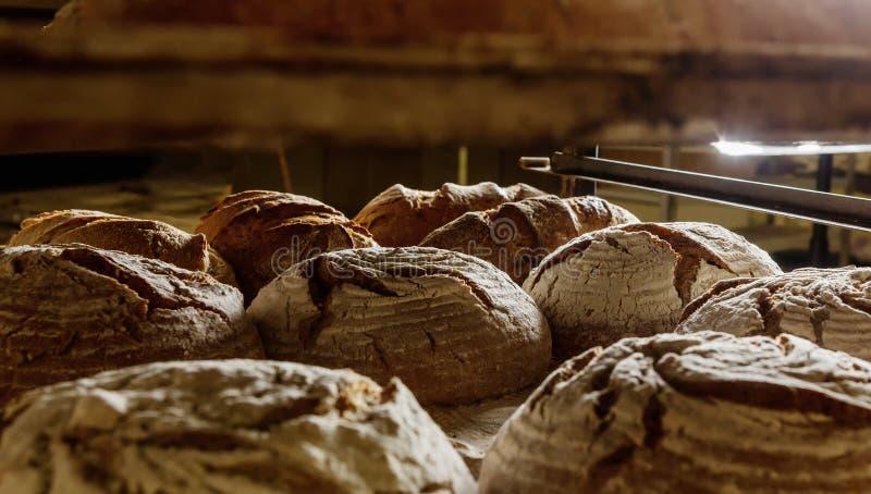 Nya bakade loaves av bröd på en kugge i ett bageri Begreppsnollan arkivbilder
