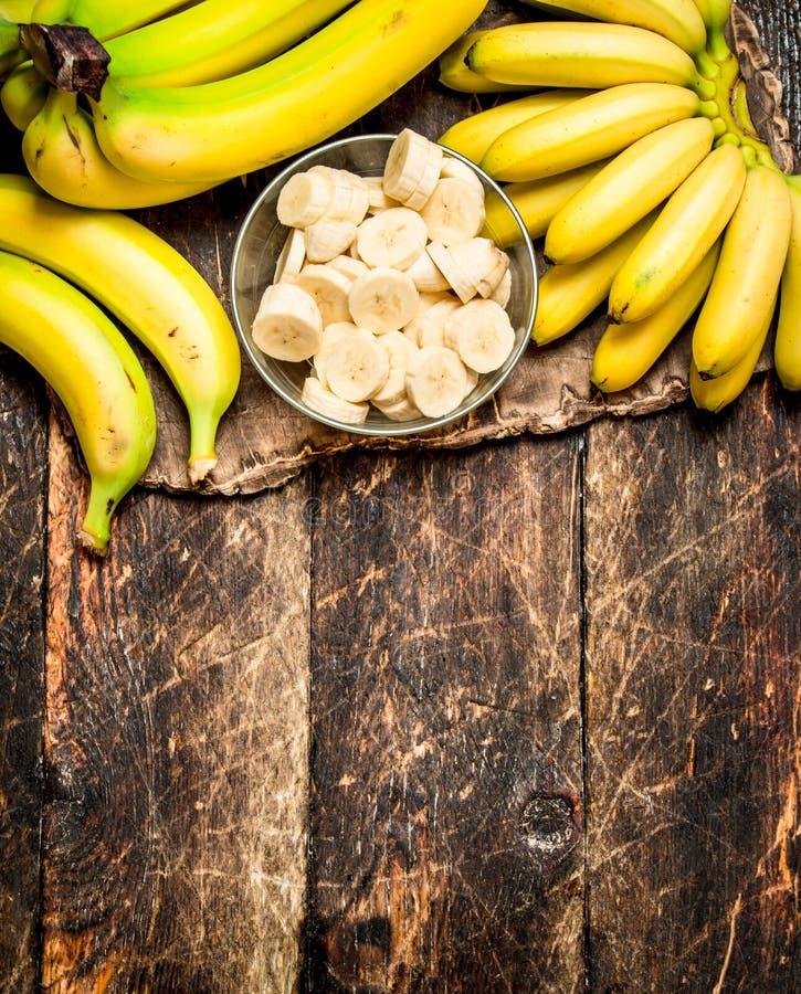 Nya bananer med högg av stycken i en bunke royaltyfri fotografi