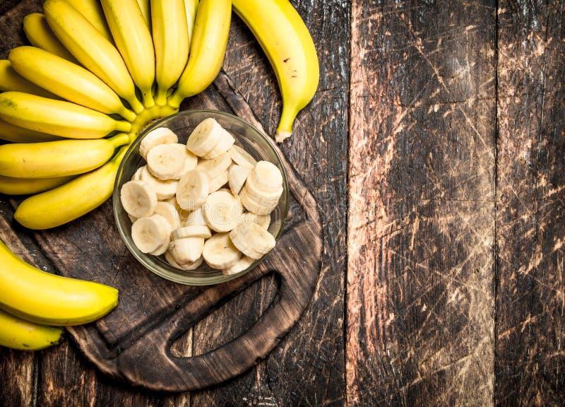 Nya bananer med högg av stycken i en bunke royaltyfria bilder