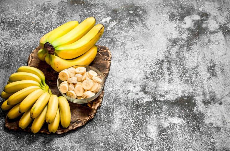 Nya bananer med stycken av skivade bananer i en bunke royaltyfri fotografi