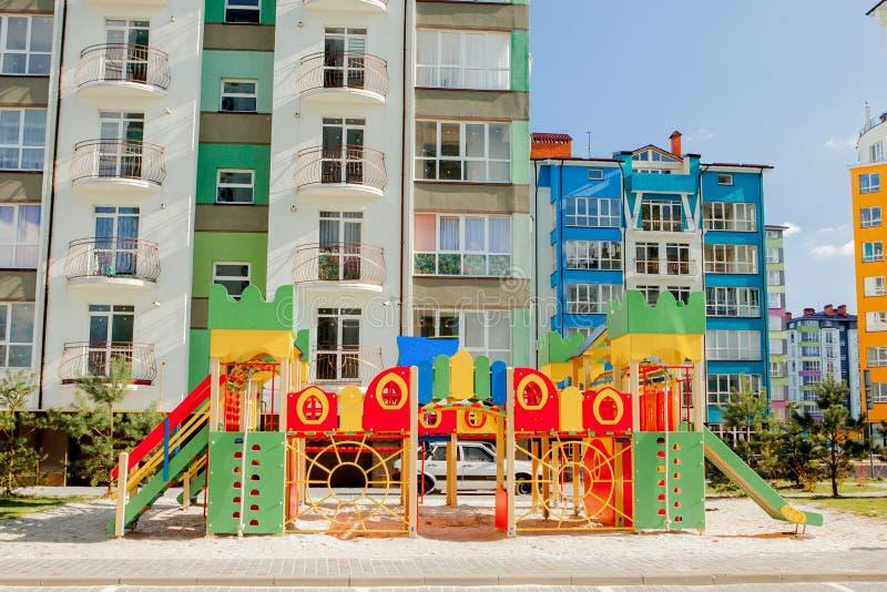Nya barns lekplats nära en lägenhetbyggnad royaltyfria foton
