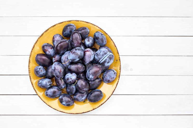 Nya blåa plommoner i gul platta på den vita trätabellen royaltyfri fotografi