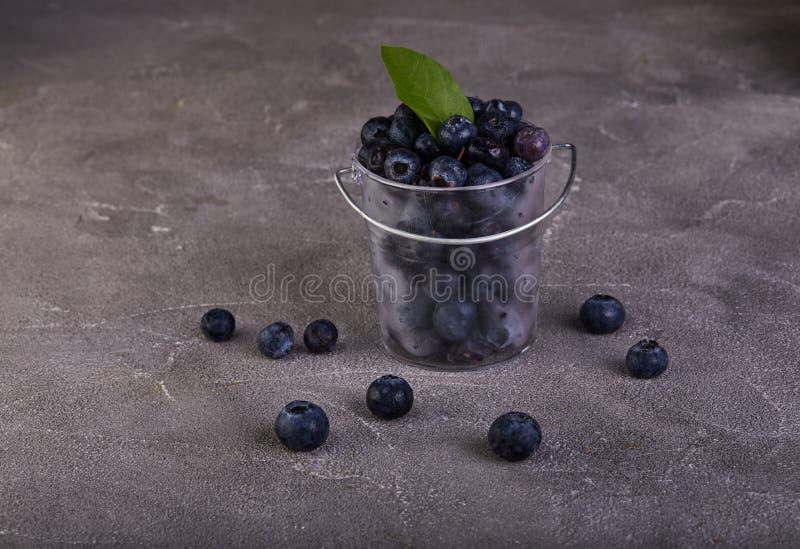 Nya blåbär i en genomskinlig hink på en grå betong royaltyfri fotografi