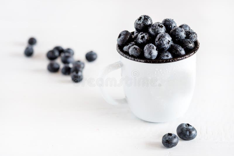 Nya blåbär i en vit rånar vit träbakgrund royaltyfria foton