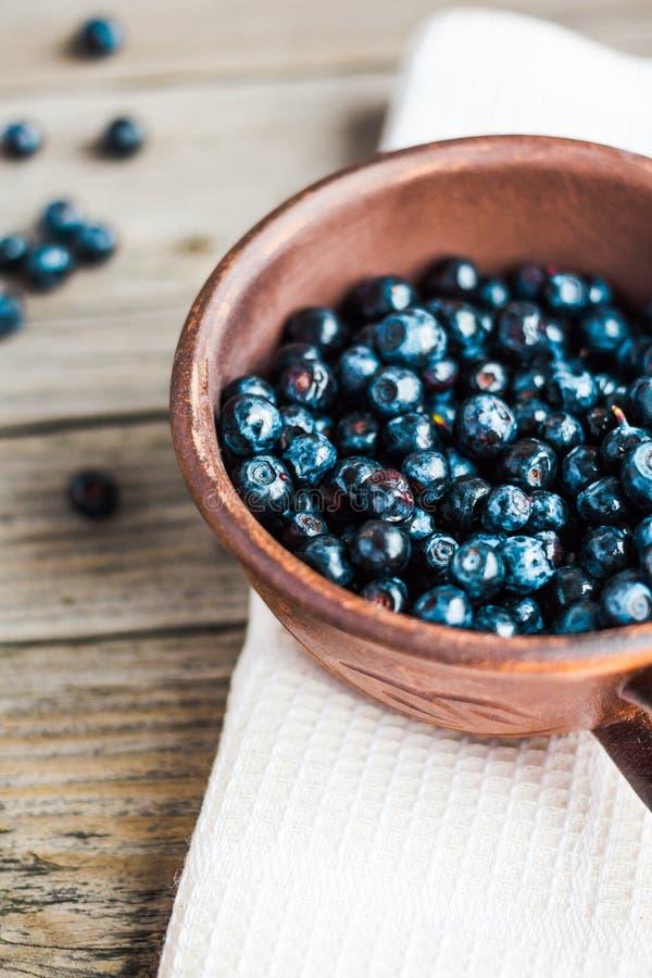 Nya blåbär i krukmakeri på grå träbakgrund, sommar, arkivbilder