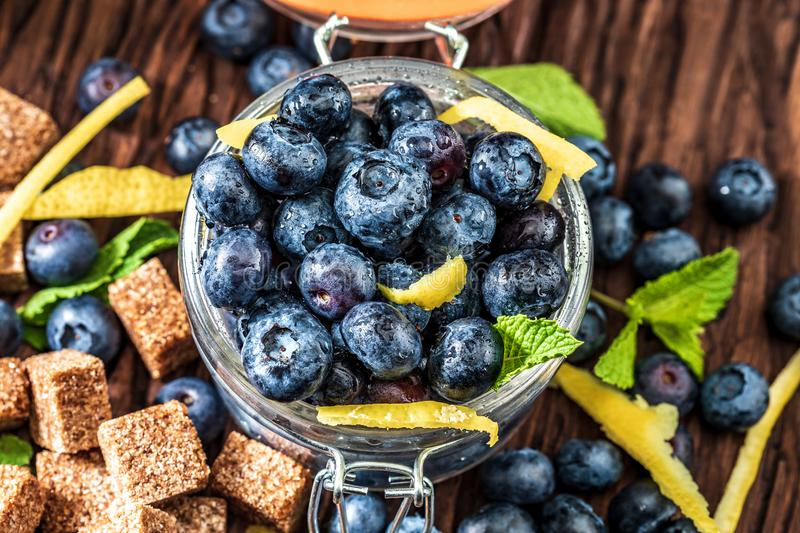 Nya blåbär, socker, citron, mintkaramell royaltyfri foto
