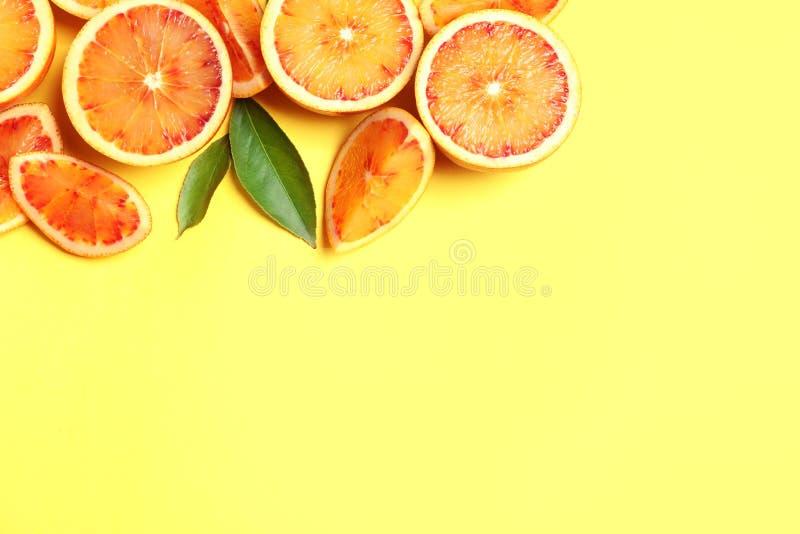 Nya blodiga apelsiner p? f?rgbakgrund, l?genhet l?gger apelsiner f?r citrusfruktcitronlimefrukter arkivbilder