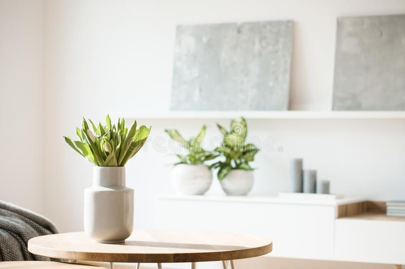 Nya blommor i den vita vasen som förläggas på en liten tabell i ljus ro royaltyfri fotografi