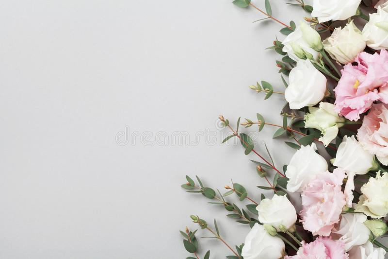 Nya blommor och gröna eukalyptussidor på grå bästa sikt för tabell lekmanna- stil för lägenhet arkivfoton