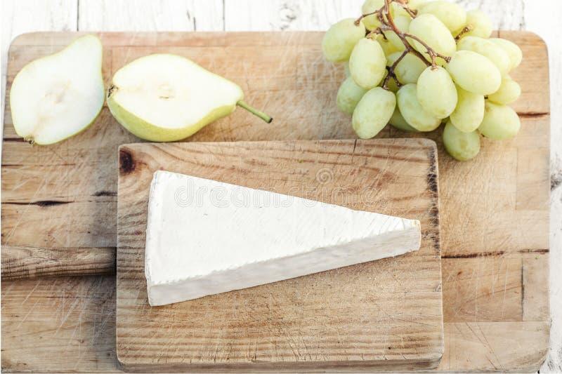 Nya Brie Cheese på skärbräda med druvor och frukter, överkant royaltyfria bilder