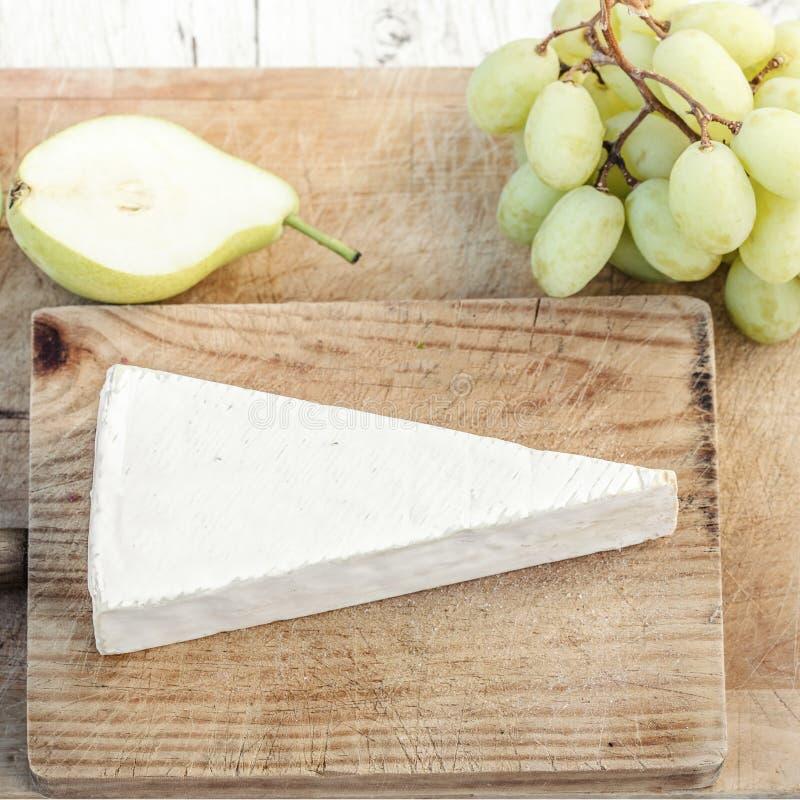 Nya Brie Cheese på skärbräda med druvor och frukter, överkant royaltyfri foto