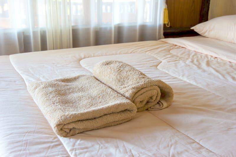 Nya bruna handdukar på säng royaltyfria bilder