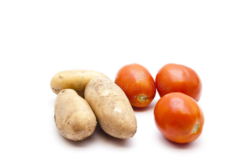 Nya bruna potatisar med tomater fotografering för bildbyråer