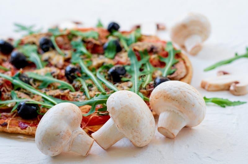 Nya champinjoner på den vita tabellen med utrymme för fri kopia på rätsidan Veggiepizza med grönsaker, oliv, rucola fotografering för bildbyråer