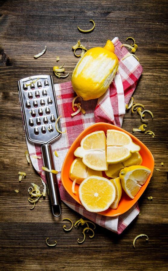 Nya citroner i bunken med piffen och rivjärn på tyg royaltyfria bilder