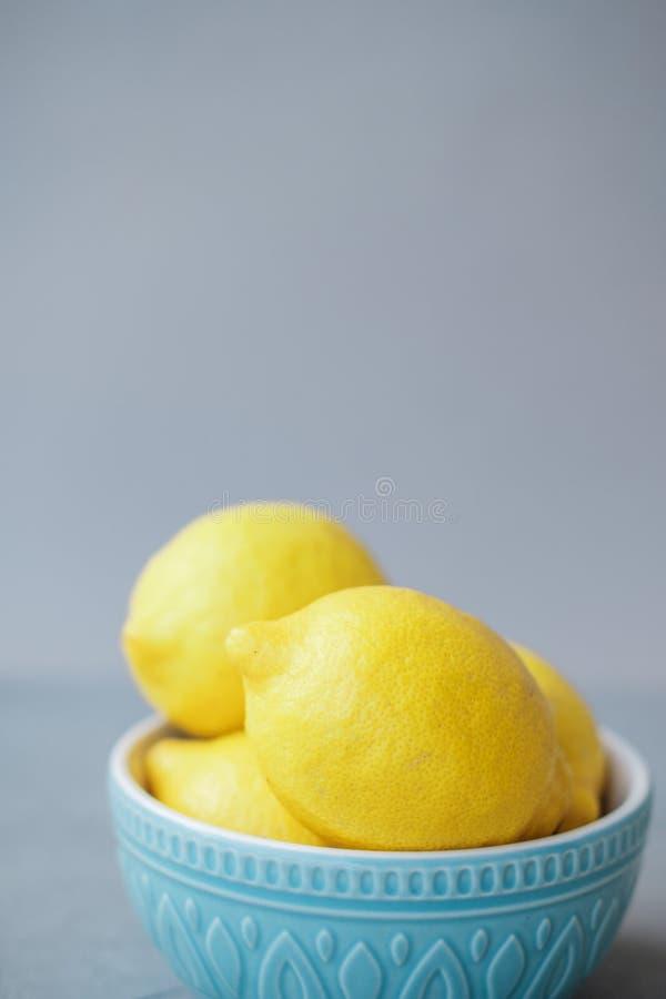 Nya citroner i en blå bunke på en grå bakgrund arkivfoton