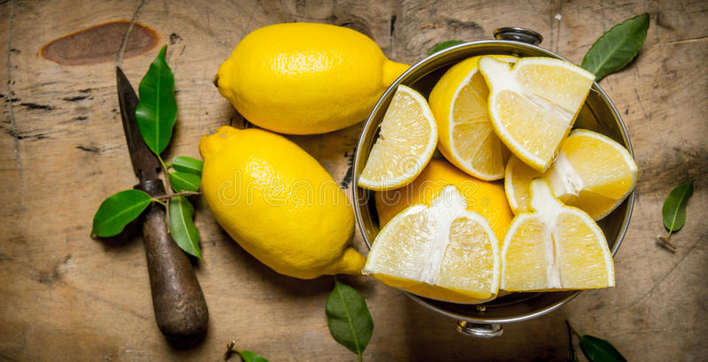 Nya citroner i en hink med sidor och kniven royaltyfri fotografi