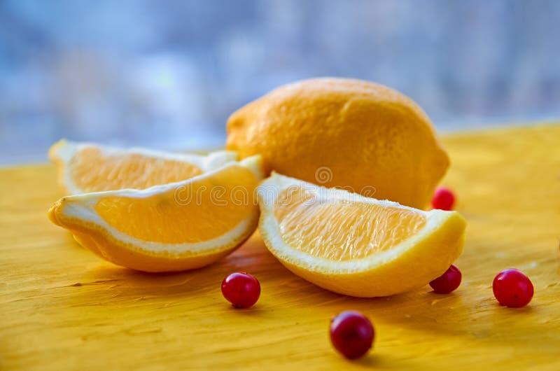 Nya citronskivor med röda bär på träbakgrundsslutet upp Ingredienser för fruktsaft eller detoxdrink på det gula brädet arkivfoto