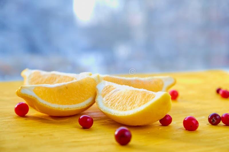 Nya citronskivor med röda bär på trätabellen med fritt suddigt kopieringsutrymme Ingredienser för sund fruktsaft eller detoxdrink fotografering för bildbyråer