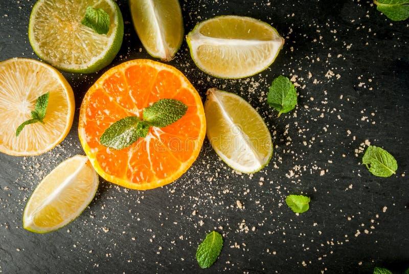 Nya citrusfrukter på en svart kritiserar tabellen royaltyfria foton