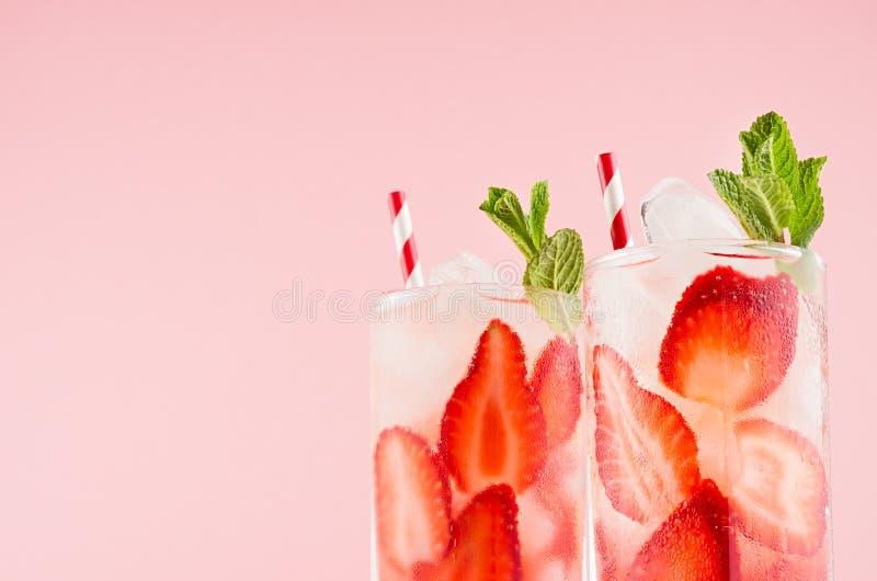 Nya drinkar för sommar med jordgubben, iskuber, den gröna mintkaramellen och randigt sugrör på den rosa väggen, closeup, bästa av arkivbilder