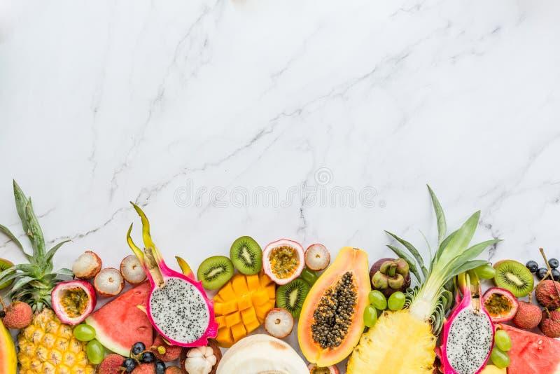 Nya exotiska frukter och tropiska palmblad på vit marmorbakgrund - papaya, mango, ananas, passionsfrukt royaltyfri fotografi